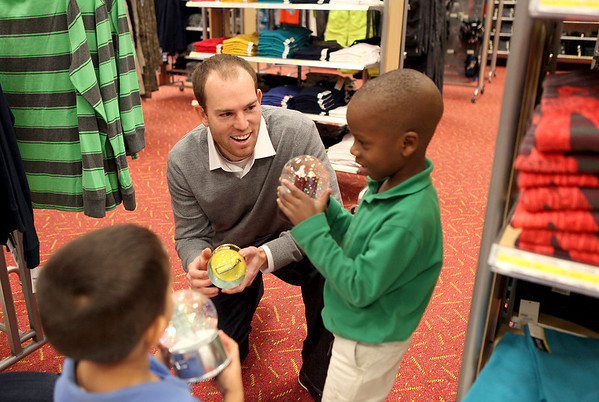 Chicago Bears kicker Robbie Gould talks with Mooseheart students Evan Tull, 5 (bottom left) and Yasin Adebayo, 6, (right) as they shop for gifts at Target in St. Charles. Over 80 Mosseheart students were each given $100 to spend courtesy of the Goulden Touch charity.(Sandy Bressner photo)
