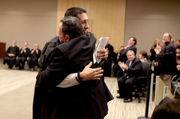 Rene Cruz of Aurora embraces his father, Florencio Cruz, after he was sworn in as the first Hispanic judge in Kane County during a ceremony Thursday at the Kane County Branch Court in St. Charles.(Sandy Bressner photo)