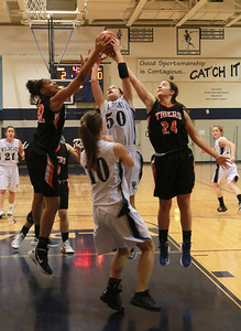Natalie Warkins of West Chicago tries to bring down a rebound as Wheaton Warrenville South's Diamond Thompson and Maggie Dansdill try to knock the ball away. Staff photo by Sarah Minor