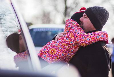Kyle Grillot - kgrillot@shawmedia.com   Brett Anderson of Cary gives his daughter Madison, 5, a hug before the start of the Merry Cary Holiday Parade Sunday in Cary. Parade participants including local businesses, community groups and organizations gather along South Wulff Street and advance down West Main Street towards Downtown Cary.