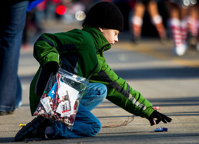 Kyle Grillot - kgrillot@shawmedia.com   Trevor Bachmann, 10, of Cary picks up candy off of West Main Street during the Merry Cary Holiday Parade Sunday in Cary. Parade participants including local businesses, community groups and organizations gather along South Wulff Street and advance down West Main Street towards Downtown Cary.
