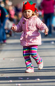Kyle Grillot - kgrillot@shawmedia.com   Corinne Schneider, 3, of Cary picks up candy off of West Main Street during the Merry Cary Holiday Parade Sunday in Cary. Parade participants including local businesses, community groups and organizations gather along South Wulff Street and advance down West Main Street towards Downtown Cary.