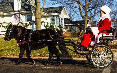 Kyle Grillot - kgrillot@shawmedia.com   Carol Swinford of Hebron rides behind Buddy the falabella miniature horse, during the 2013 Kiwanis Santa Run in Downtown Crystal Lake. Proceeds from the race go towards Turning Point Big Bros & Sis, CASA Light Center Foundation, Main Stay, Girls on the run and Kiwanis of MCCO.