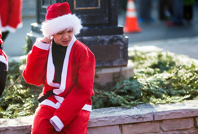 Kyle Grillot - kgrillot@shawmedia.com   Sam Deweerdt, 8,  of Hoffman Estates waits on Williams Street before the start of the 2013 Kiwanis Santa Run in Downtown Crystal Lake. Proceeds from the race go towards Turning Point Big Bros & Sis, CASA Light Center Foundation, Main Stay, Girls on the run and Kiwanis of MCCO.