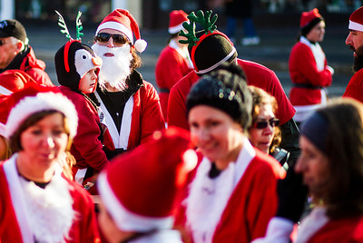 Kyle Grillot - kgrillot@shawmedia.com   Beth Irwin of Genoa City, Wis., (top-left) holds her son Jacob, 4, before the start of the 2013 Kiwanis Santa Run in Downtown Crystal Lake. Proceeds from the race go towards Turning Point Big Bros & Sis, CASA Light Center Foundation, Main Stay, Girls on the run and Kiwanis of MCCO.