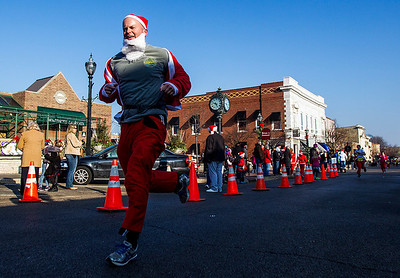 Kyle Grillot - kgrillot@shawmedia.com   John Verchoto of Crystal Lake advances down North Williams Street towards the finish line during the 2013 Kiwanis Santa Run in Downtown Crystal Lake. Proceeds from the race go towards Turning Point Big Bros & Sis, CASA Light Center Foundation, Main Stay, Girls on the run and Kiwanis of MCCO.