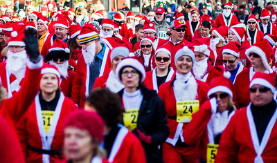 Kyle Grillot - kgrillot@shawmedia.com   Runners advance down North Williams Street just after the the start of the 2013 Kiwanis Santa Run in Downtown Crystal Lake. Proceeds from the race go towards Turning Point Big Bros & Sis, CASA Light Center Foundation, Main Stay, Girls on the run and Kiwanis of MCCO.