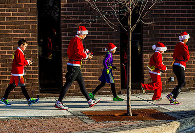 Kyle Grillot - kgrillot@shawmedia.com   The Deweerdt's of Hoffman Estates (from left) Jack, 12, Jeff, Ben, 10, Sam, 8, and Stacey, rush towards Williams Street before the start of the 2013 Kiwanis Santa Run in Downtown Crystal Lake. Proceeds from the race go towards Turning Point Big Bros & Sis, CASA Light Center Foundation, Main Stay, Girls on the run and Kiwanis of MCCO.