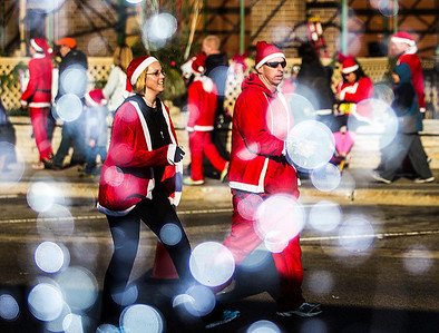 Kyle Grillot - kgrillot@shawmedia.com   Kristen Carlstedt (left) and Bryan Bode both of Crystal Lake advance down North Williams Street towards the finish line during the 2013 Kiwanis Santa Run in Downtown Crystal Lake. Proceeds from the race go towards Turning Point Big Bros & Sis, CASA Light Center Foundation, Main Stay, Girls on the run and Kiwanis of MCCO.