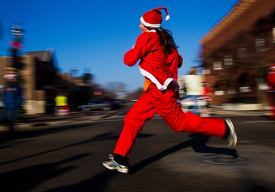 Kyle Grillot - kgrillot@shawmedia.com   A runner advances down North Williams Street towards the finish line during the 2013 Kiwanis Santa Run in Downtown Crystal Lake. Proceeds from the race go towards Turning Point Big Bros & Sis, CASA Light Center Foundation, Main Stay, Girls on the run and Kiwanis of MCCO.