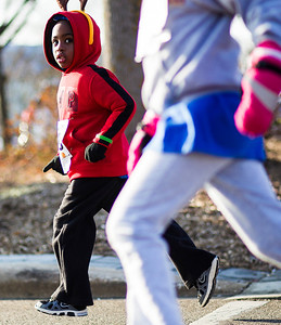 Kyle Grillot - kgrillot@shawmedia.com   William Ogonga, 4, of Crystal Lake looks to his competition during the 2013 Kiwanis Santa Run in Downtown Crystal Lake. Proceeds from the race go towards Turning Point Big Bros & Sis, CASA Light Center Foundation, Main Stay, Girls on the run and Kiwanis of MCCO.