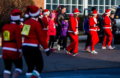 Kyle Grillot - kgrillot@shawmedia.com   Race participants head towards the starting line before the 2013 Kiwanis Santa Run in Downtown Crystal Lake. Proceeds from the race go towards Turning Point Big Bros & Sis, CASA Light Center Foundation, Main Stay, Girls on the run and Kiwanis of MCCO.