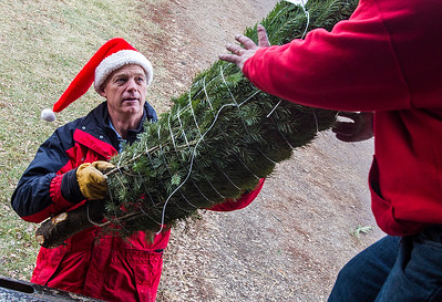 Kyle Grillot - kgrillot@shawmedia.com   George Richardson hands Don Stupienski a christmas tree to load onto a truck at the Richardson Farm Monday in Spring Grove. The Richardson's mission is to donate approximately 75 fresh-cut Christmas trees, which will be shipped to American military families at domestic and foreign bases worldwide. While thousands of trees donated to Trees for Troops are donated by American Christmas tree growers such as the Richardsons, individuals can support the program by making donations at participating tree farms or online.