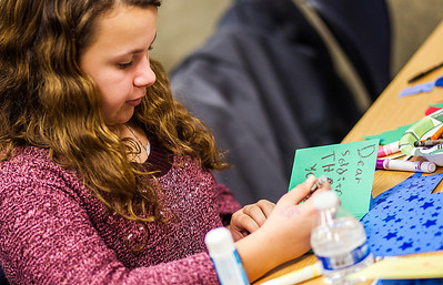 Kyle Grillot - kgrillot@shawmedia.com   Abby McComb, 12, of Algonquin creates cards for wounded and overseas soldiers during the Holiday Mail for Heroes event Tuesday at the Algonquin Area Public Library.  All cards are sent through the American Red Cross to overseas and wounded American soldiers.