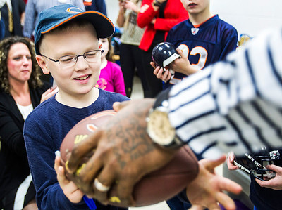Kyle Grillot - kgrillot@shawmedia.com   Zach Benton,7, of McHenry receives his signed football from Martellus Bennett during the autograph signing at Sage YMCA Tuesday in Crystal Lake. In order to get an autograph spectators bring an unwrapped new toy or non-persihable food item to benefit Toys for Tots and McHenry County food pantries.
