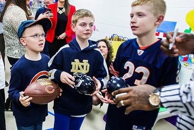 Kyle Grillot - kgrillot@shawmedia.com   Zach Benton, 7, Andrew Heilman, 11, and Adam Benton, 11,  receives his signed merchandise from Martellus Bennett during the autograph signing at Sage YMCA Tuesday in Crystal Lake. In order to get an autograph spectators bring an unwrapped new toy or non-persihable food item to benefit Toys for Tots and McHenry County food pantries.