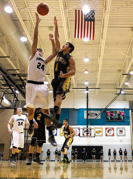 Kyle Grillot - kgrillot@shawmedia.com   Woodstock North senior Nikolaus Herscha (24) puts up a shot user the defense of Harvard senior Fernando Carrera  during the third quarter of the high school basketball game between Woodstock North and Harvard Wednesday in Woodstock. Woodstock North won the game 61-48.