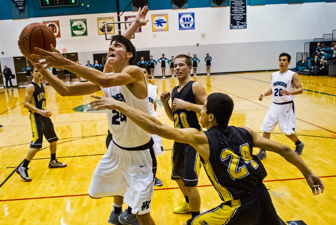 Kyle Grillot - kgrillot@shawmedia.com   Woodstock North senior Nikolaus Herscha (24) puts up a shot under the defense of Harvard senior Zach Martin during the second quarter of the high school basketball game between Woodstock North and Harvard Wednesday in Woodstock. Woodstock North won the game 61-48.
