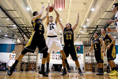 Kyle Grillot - kgrillot@shawmedia.com   Woodstock North senior Nikolaus Herscha (24) puts up a shot user the defense of Harvard seniors Tate Miller (23) and Justin Nolan (2) during the third quarter of the high school basketball game between Woodstock North and Harvard Wednesday in Woodstock. Woodstock North won the game 61-48.