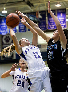 Sarah Nader- snader@shawmedia.com Woodstock's Colleen Brown (left) shoots over Woodstock North's Samantha Abbate during the first quarter of Thursday's game in Woodstock December 5, 2013. Woodstock won, 52-58.