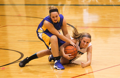 Sarah Nader- snader@shawmedia.com Johnsburg's Erika Szramek (left) and Woodstock North's Jenifer Crain fight for control of the ball during the second  quarter of Friday's game in Woodstock December 6, 2013. Johsnburg won, 43-38.