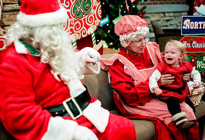 Sarah Nader- snader@shawmedia.com Zoe Leras, 1, of Pingree Grove takes a photo with Santa and Mrs. Claus during the 11th annual Festival of Trees at the Lake in the Hills Village Hall Friday, December 6, 2013. After the lighting of the 20 sponsored trees, families went inside for cookies and a photo opportunity with Santa.