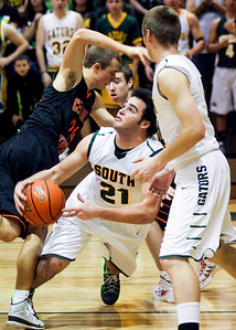 Sarah Nader- snader@shawmedia.com Crystal Lake South's Austin Rogers (center) is fouled on during the third quarter of Saturday's game against Crystal Lake Central in Crystal Lake December 7, 2013.