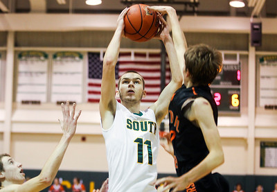 Sarah Nader- snader@shawmedia.com Crystal Lake South's Chris Mahoney (left) shoots over Crystal Lake Central's Jason Price during the third quarter of Saturday's game in Crystal Lake December 7, 2013.