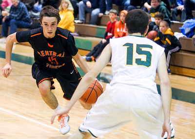 Sarah Nader- snader@shawmedia.com Crystal Lake Central's Derek Olson (left) dribbles past Crystal Lake South's Tyler Baker during the third quarter of Saturday's game in Crystal Lake December 7, 2013.