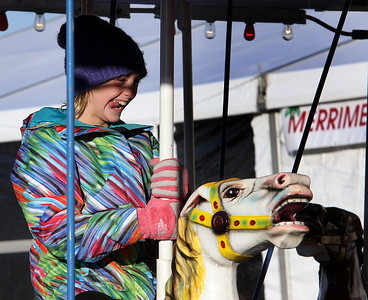 Jeff Krage – For Shaw Media Eliza Perry, 10, of Barrington rides the carousel during Saturday's Christkindl Festival in downtown Barrington. Barrington 12/7/13