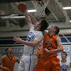 St.Charles North's Jack Callaghan puts up a reverse layup against St.Charles East's James McQuillan at St.Charles North High School in St.Charles, IL on Saturday, December 07, 2013 (Sean King for Shaw Media)