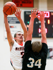 Sarah Nader- snader@shawmedia.com McHenry's Cody Freund (left) shoots over Woodstock North's Doug Devore during the first quarter of Tuesday's game in McHenry December 10, 2013. McHenry won, 60-50.