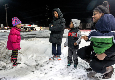 Sarah Nader- snader@shawmedia.com Leah Taylor (left), 3, Maurice Hardy, 7,  and Denzel Hardy, 2, play outside of McDonalds in McHenry with their mother, Rachel Hardy and brother, Issace Taylor, 1, on Wednesday, December 11, 2013. The family has been living at Home of the Sparrow since May and will soon be homeless when the family has to leave Home of the Sparrow.