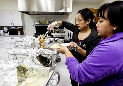 Sarah Nader- snader@shawmedia.com Iris Sagrado (left) of Westmont and her sister, Ivy Sagrado of Woodstock load up a plate with food while preparing and serving dinner at PADS in Woodstock Wednesday, December 11, 2013. This is the third season the Sagrado's have volunteered at PADS.