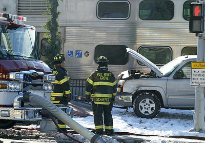 H. Rick Bamman -hbamman@shawmedia.com Fox River Grove firefighters stand by at the scene following an accident involving a pickup truck and a METRA train at Lincoln Av. and Rt. 14 Thursday.