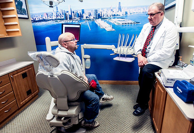 Sarah Nader- snader@shawmedia.com Dr. Timothy Stirneman (right) talks with Joe Hathcoat, a truck driver suffering from severe sleep apnea before fitting  him with an oral mouthpiece that will hold his jaw forward allowing him to have a larger airway at All Smiles Dental in Algonquin Tuesday, December 17, 2013. The mouthpieces are used for those with sleep apnea who can't tolerate the large breathing masks that must be worn at night.