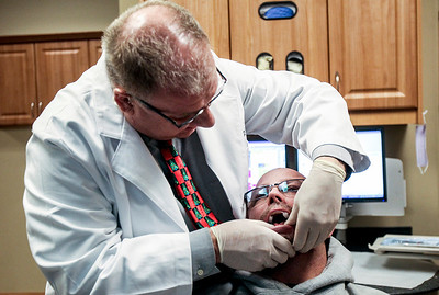 Sarah Nader- snader@shawmedia.com Dr. Timothy Stirneman fits Joe Hathcoat, a truck driver suffering from severe sleep apnea with an oral mouthpiece that will hold his jaw forward allowing him to have a larger airway at All Smiles Dental in Algonquin Tuesday, December 17, 2013. The mouthpieces are used for those with sleep apnea who can't tolerate the large breathing masks that must be worn at night.