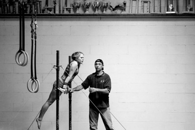 Sarah Nader- snader@shawmedia.com Coach Lee Battaglia spots Jada Berkland while she works on a move on the uneven bars during gymnastic practice at Crystal Lake Gymnastics Training Center Monday, December 16, 2013.