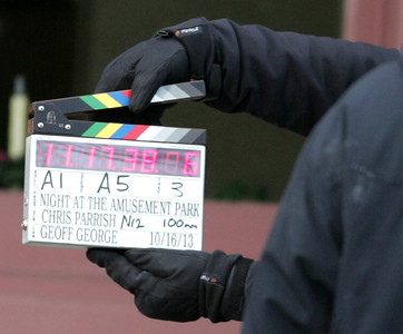 """H. Rick Bamman -hbamman@shawmedia.com A crew member of the film """"Night at the Amusement Park,"""" slates a scene to be filmed in front of the Woodstock Opera House on Monday. The film is being directed by Chris Parrish, a Woodstock High School graduate."""