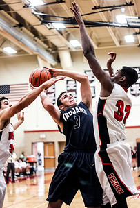 Sarah Nader- snader@shawmedia.com Cary-Grove's Tyler Szydlo (left) tries to shoot over Huntley's Amanze Egekeze during the third quarter of Tuesday's game in Huntley December 17, 2013. Huntley defeated Cary-Grove, 58-25.