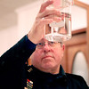 Kane County Sheriff Pat Perez looks at the clarity of a water sample during the Kane County Water Association's annual Water Taste Test Contest for the Best Tasting Water in Kane County at the Lincoln Inn in Batavia Thursday. Water samples from St. Charles, Batavia, Geneva, Elgin, Aurora, North Aurora, Sugar Grove, Yorkville and Montgomery were judged.