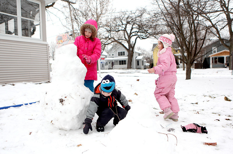 (Left to right) Evelyn, 10, Jude, 3, and Clare Zielinski, 5, build a snowman in the front yard of their Batavia home Thursday afternoon.