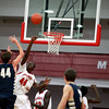 Mooseheart's Akim Nyang (center) blocks the shot of Harvest Christian Academy's John Vislisel during their game at Mooseheart Tuesday night.