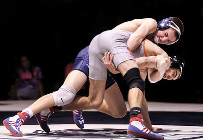 Sarah Nader- snader@shawmedia.com Cary-Grove's John Cullen (left) wraps his arms around McHenry's Rob Nagel in the 132-pound match Thursday, December 19, 2013 in Cary. McHenry won the dual 32-29.