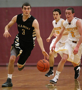 Brett Moist/ for the Northwest Herald    Sycamore's Maxx Miller drives past Richmond Burton's Blaine Bayer  during the 2nd quarter of their day one matchup of the  64th annual E.C. Nichols basketball tournament at Marengo High School on Saturday.