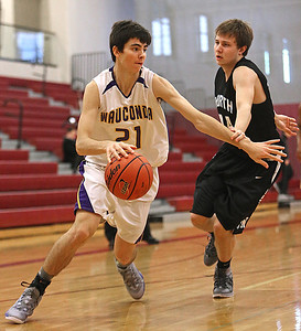 Brett Moist/ for the Northwest Herald    Wauconda's Matt Bulgarelli drives past  Woodstock North's Evan Peterson during the 3rd quarter of their day one matchup of the  64th annual E.C. Nichols basketball tournament at Marengo High School on Saturday.