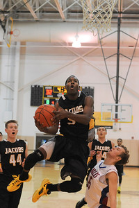 Jacobs junior guard Chris Orange goes up for a lay up past Lakes junior guard Benett Haviland during their opening rounf game of the Hinkle Holiday Classic at Jacobs high school.