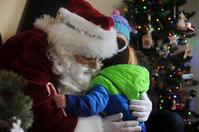 Santa Clause hugs Cayden Rippentrop,2, of Crystal Lake, Il., at the Santa House in downtown Crystal Lake,Il. after spending the day visiting with children Sunday December 22,2013 . The house, which opened in 2008, is open every weekend starting the week after Thanksgiving until the December 23rd.