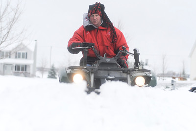 Ian Maule - For Shaw Media Brett Bullamore, of Johnsburg, Il, uses a four wheeler to plow his driveway Sunday morning ,Decemeber 22,2013, in Johnsburg,Il. McHenry County got between 3-6 inches of snow starting last night and into the morning.