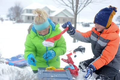 Ian Maule - For Shaw Media Garrett,8, and Hailey Bullamore,11, both of Johnsburg,Il., look through a box of supplies while building snowmen Sunday morning ,Decemeber 22,2013, in Johnsburg,Il. McHenry County got between 3-6 inches of snow starting last night and into the morning.